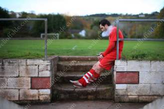 A Teignmouth player smokes a cigarette and looks at his mobile phone after the match