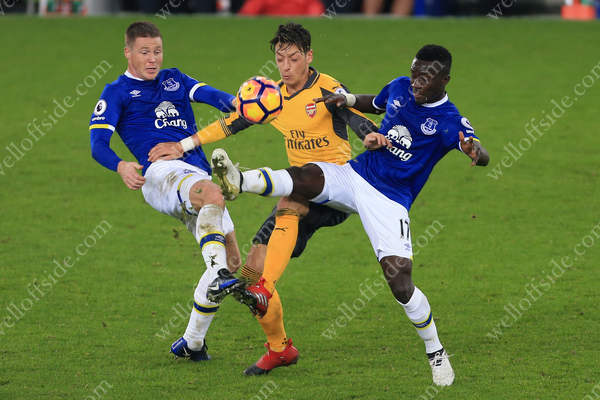Mesut Ozil of Arsenal battles with James McCarthy of Everton (L) and Idrissa Gueye of Everton