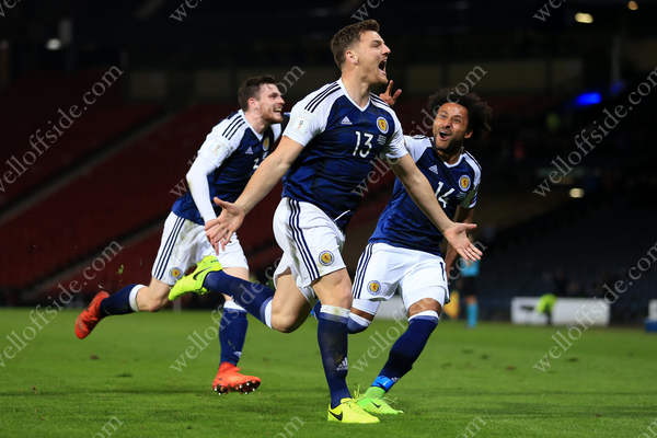 Chris Martin celebrates his late winner for Scotland, flanked by teammates Andrew Roberton (L) and Ikechi Anya (R)