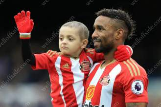 Jermain Defoe of Sunderland carries terminally-ill young Sunderland fan Bradley Lowery out onto the pitch as the mascot for their match at Everton