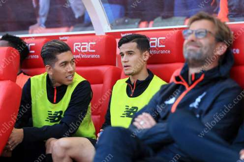 Roberto Firmino of Liverpool (L) and teammate Philippe Coutinho start the match as substitutes, sitting behind Liverpool manager Jurgen Klopp