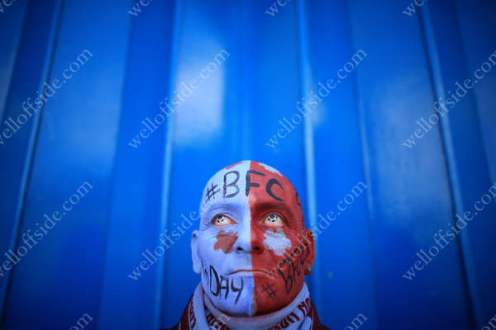 A Burnley fan with a painted face and football contact lenses in his eyes
