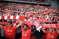 Liverpool fans hold heir scarves aloft as they sing 'You'll Never Walk Alone'