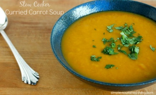 Slow Cooker Curried Carrot Soup in blue bowl garnished with fresh chopped cilantro.