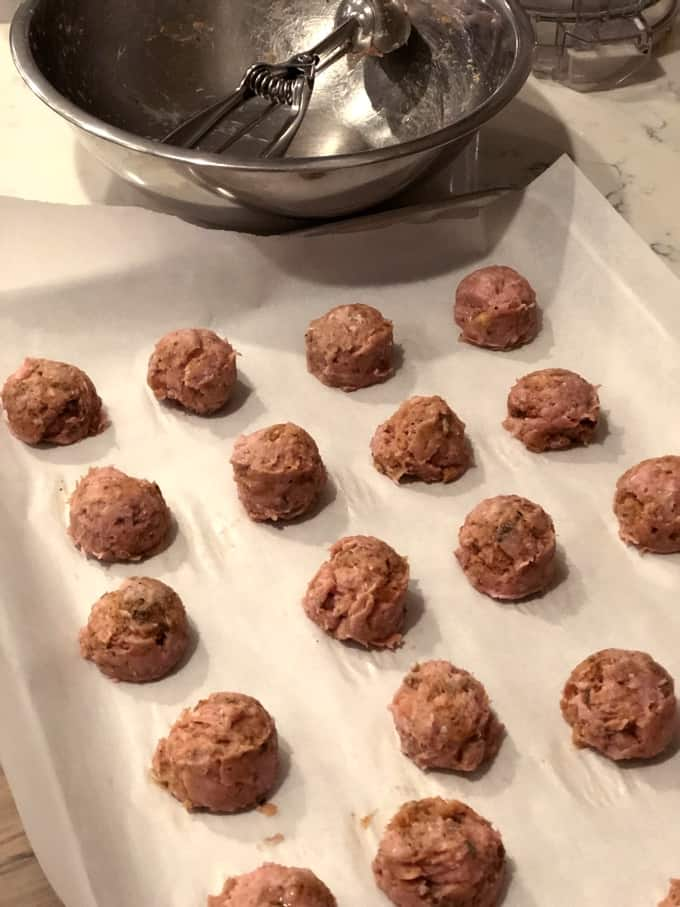 Turkey Sriracha meatballs on a parchment-lined baking sheet with cookie scoop and bowl in the background