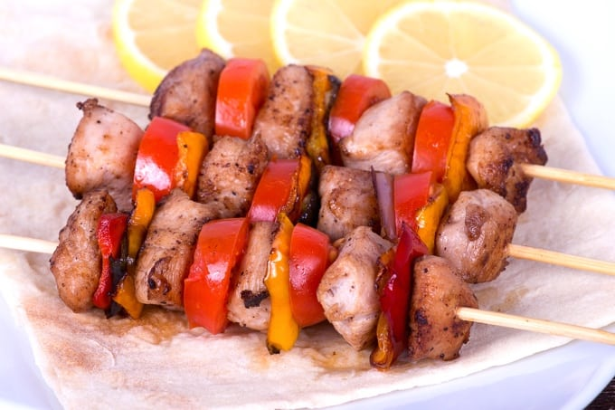 Tasty grilled pork and vegetable skewers on plate with lemon slices