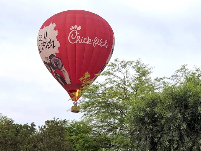 Red Chick-fil-A hot air balloon over some trees.