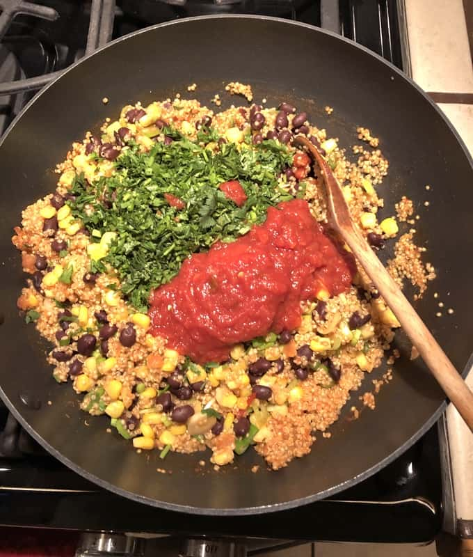 Stirring in chopped cilantro and salsa to Southwestern Quinoa Skillet with wooden spoon.
