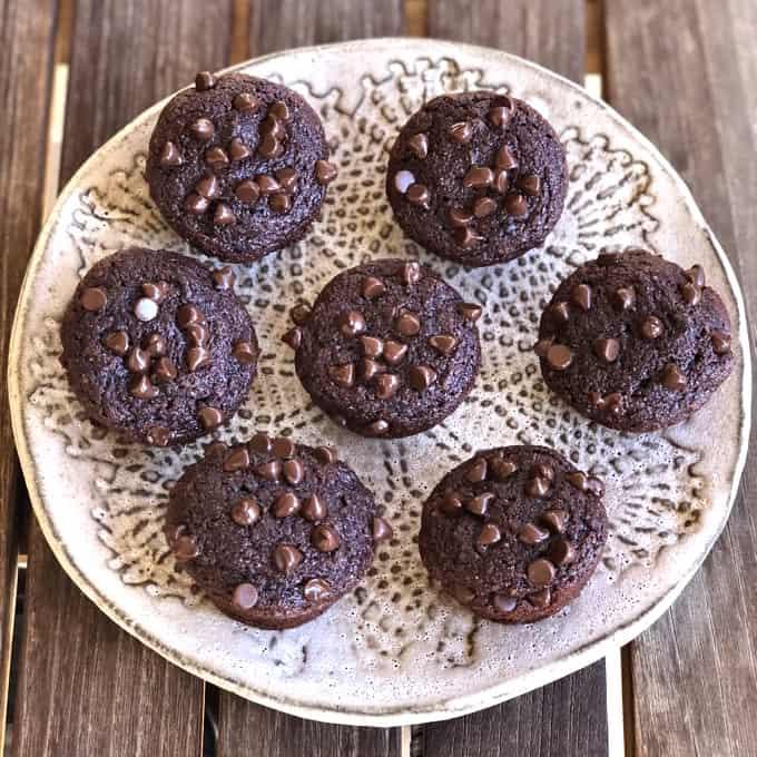 Mini beet brownie bites on ceramic plate on wooden table.