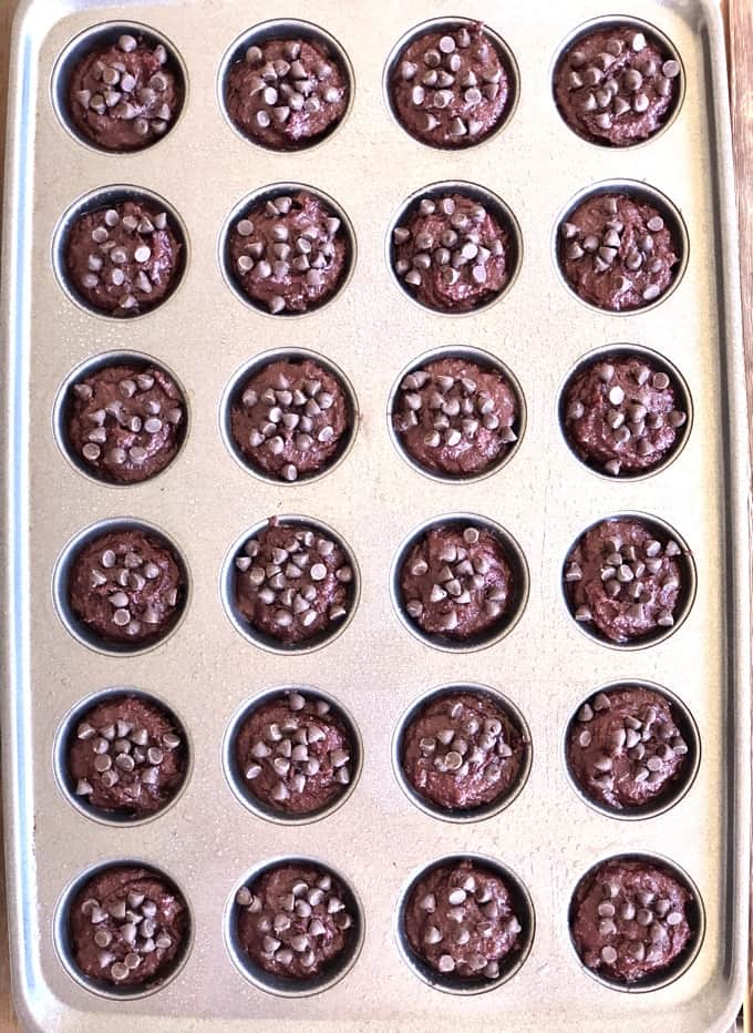 Unbaked mini beet brownies topped with chocolate chips in muffin tin.