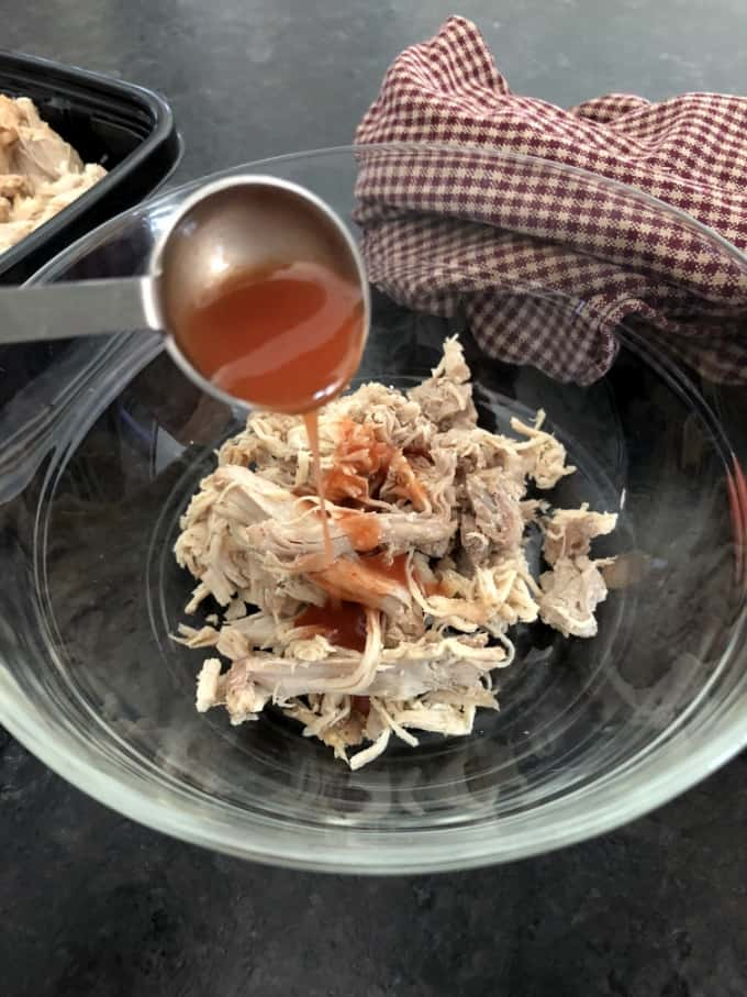 Adding hot wing sauce to shredded chicken in glass bowl.