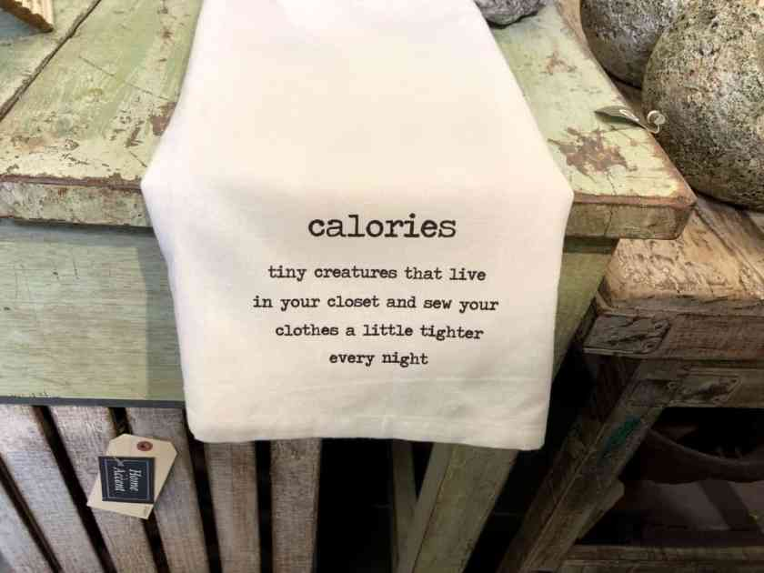 Table linen with saying about calories and weathered green table.
