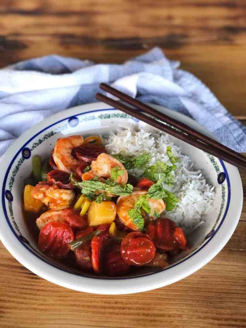 Caribbean Shrimp with Pineapple and Mixed Vegetables in bowl with white rice and chopsticks on wood table.