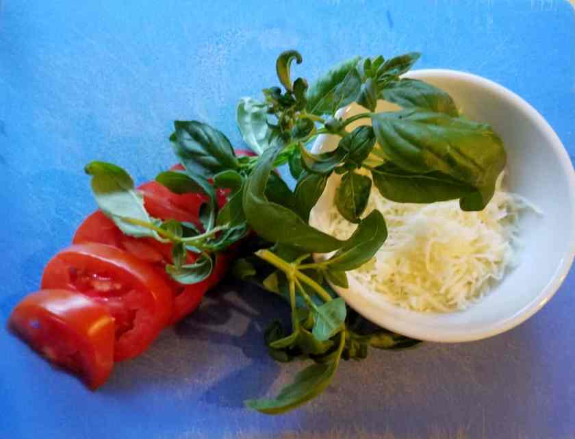 Sliced tomatoes, bunch of basil leaves and shredded mozzarella on blue cutting mat.