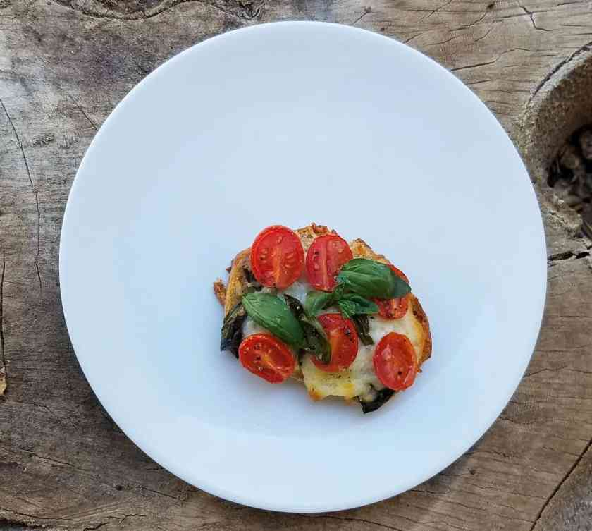Toasted caprese sandwich on white plate from above.
