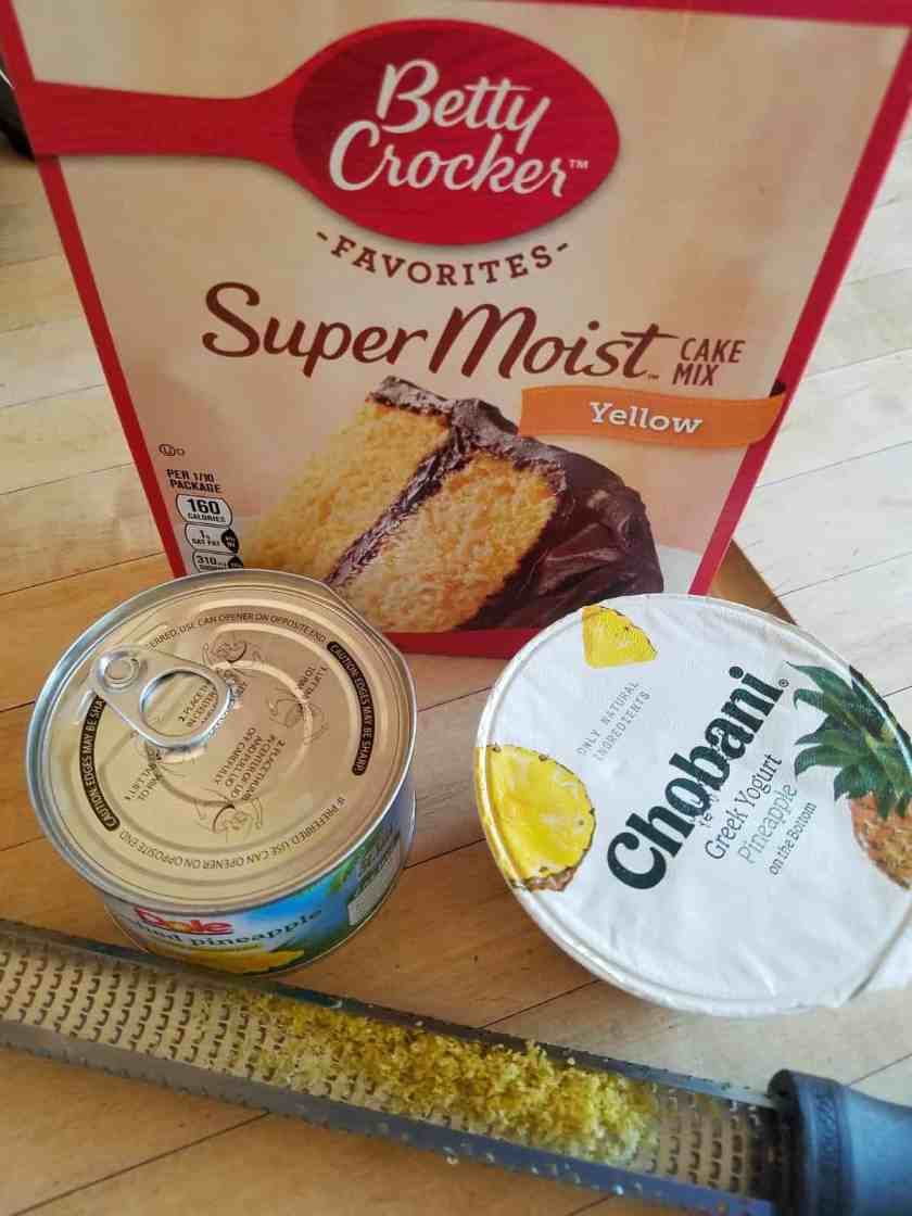 Box of supermoist yellow cake mix, can of crushed pineapple, container of pineapple greek yogurt and lemon zester on counter.