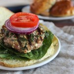 spinach and feta turkey burger on a roll with onions