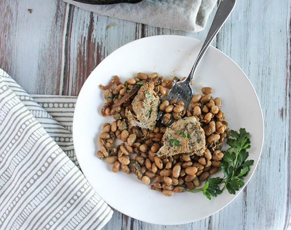 Cut up pieces of chicken and white beans on a white plate