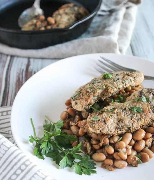 chicken piled on top of beans on a white plate
