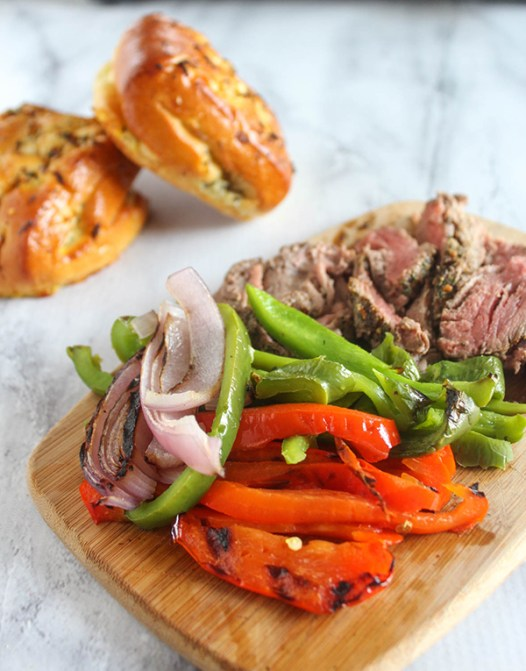 peppers onions and steak on a cutting board with rolls in background