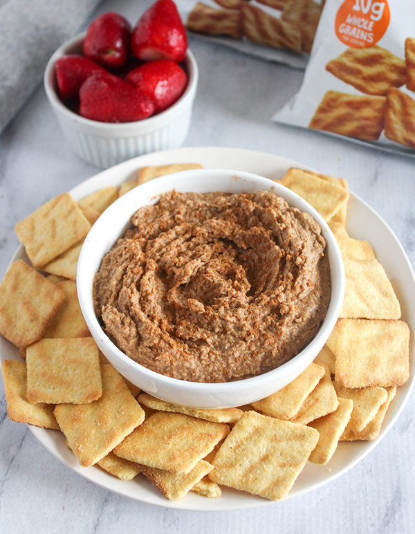 snickerdoodle hummus in a bowl with cornbread crisps and strawberries