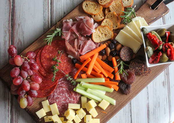 a view looking down at the meat and cheese board an assortment of salami, pepperoni, cheese, carrot sticks and celery