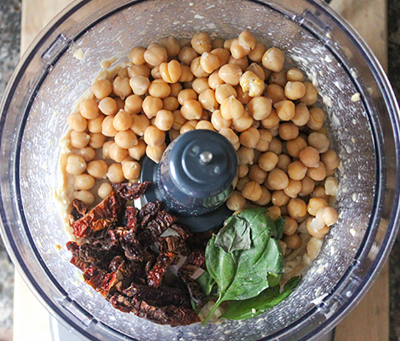 Chickpeas, sun dried tomaotes and basil in a food processor bowl