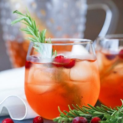Two glasses of cranberry punch on a blue tablecloth with pitcher in the background
