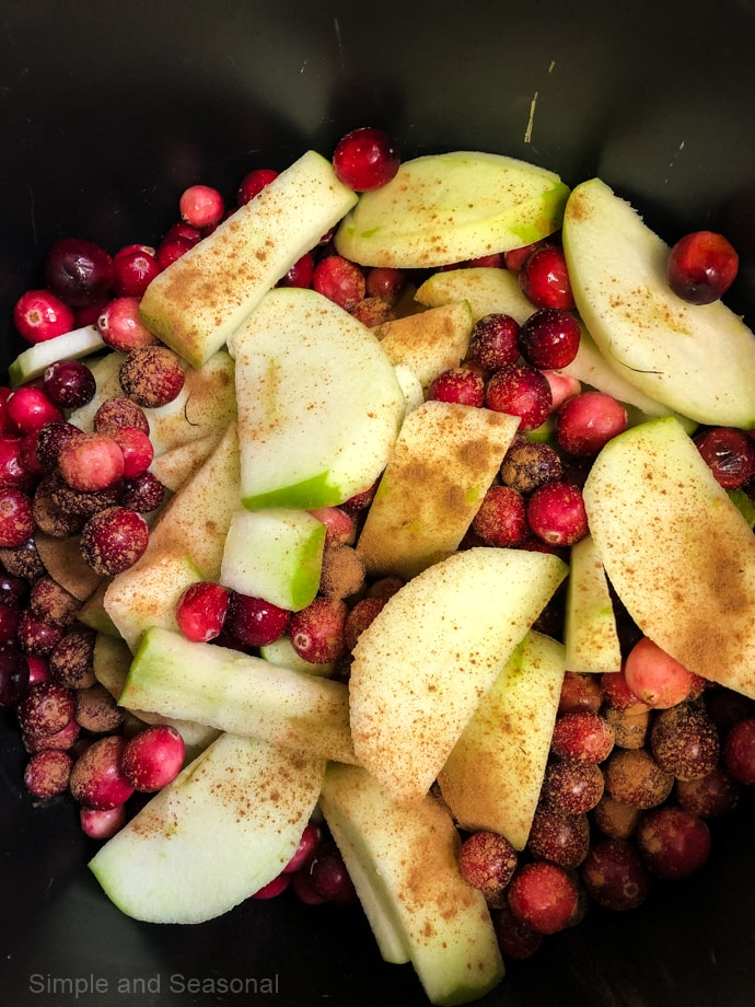 pot filled with apple slices, cranberries and cinnamon