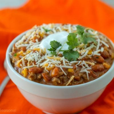 closeup of bowl of taco soup topped with cheese, sour cream and cilantro
