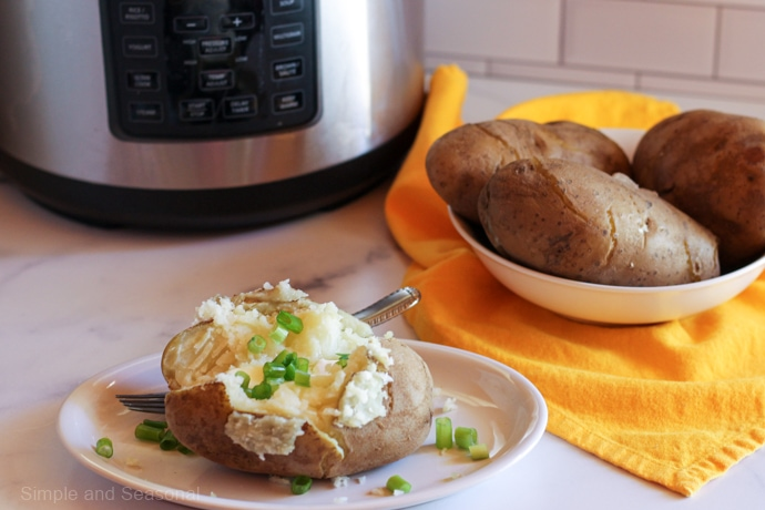 cooked potato on plate with 3 cooked potatoes in a large bowl