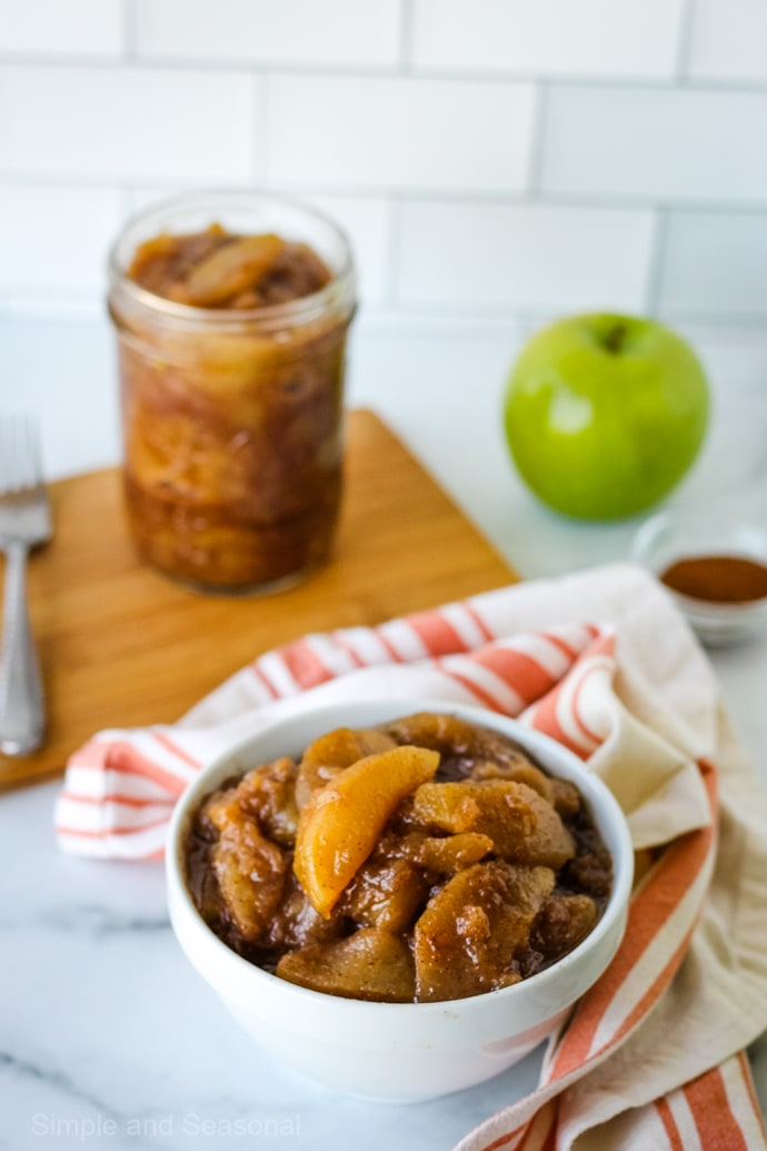 bowl of crockpot express apple pie filling with jar in the background