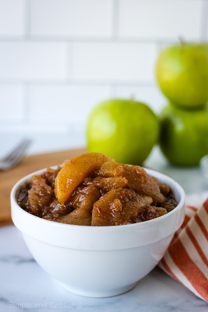 apple pie filling in a white bowl (closeup on apple slice)