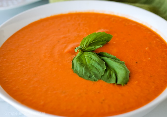 closeup on soup in bowl with fresh basil leaf garnish