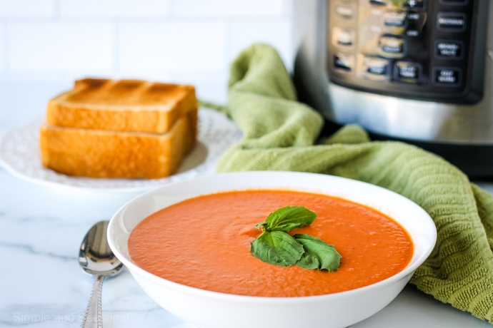 bowl of soup, with plate of grilled cheese and Crockpot Express in the background
