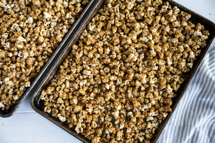 cooked caramel corn cooling on sheet pans