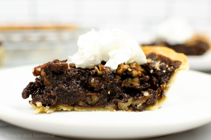 slice of chocolate pecan pie with whipped cream