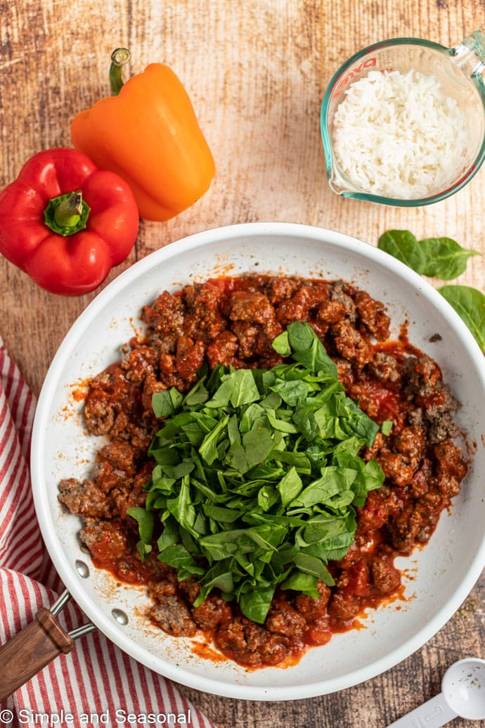 beef mixture with sauce and spinach in bowl