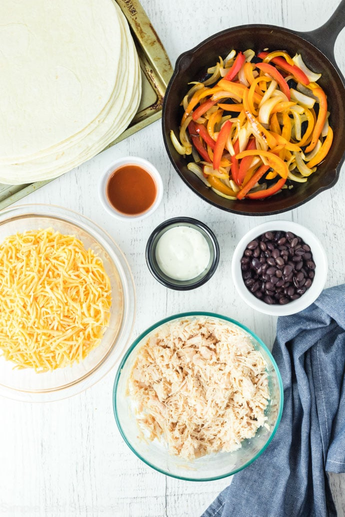 cheese, tortillas, chicken, sauce and peppers- ingredients for sheet pan buffalo chicken quesadillas