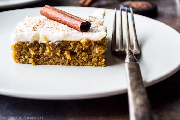slice of pumpkin sheet cake on a white plate with fork next to it