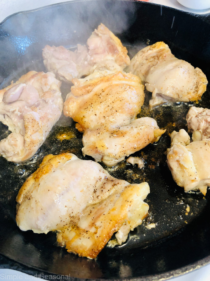 chicken pieces browning in a skillet