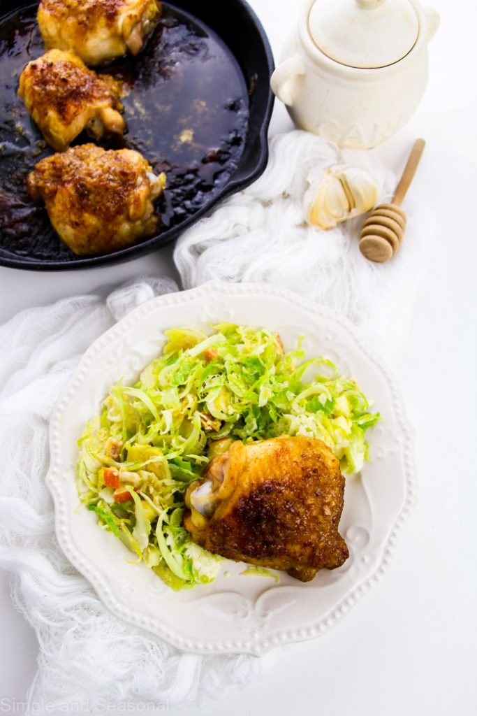top down view of cooked chicken on a plate with salad and skillet filled with more chicken