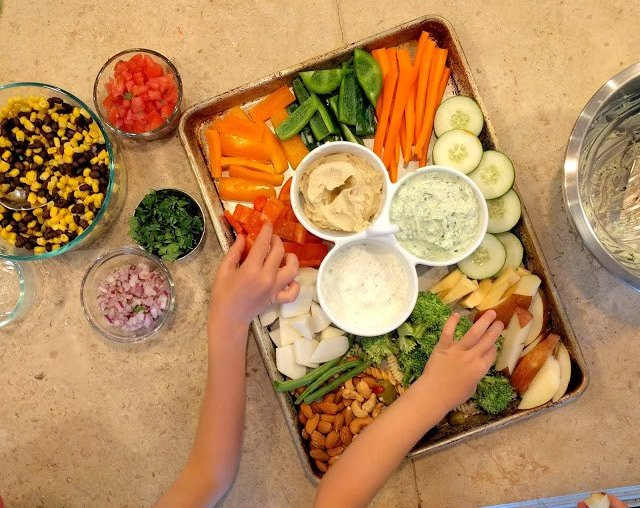 Sheet pan full of vegetables, nuts, meat and dips