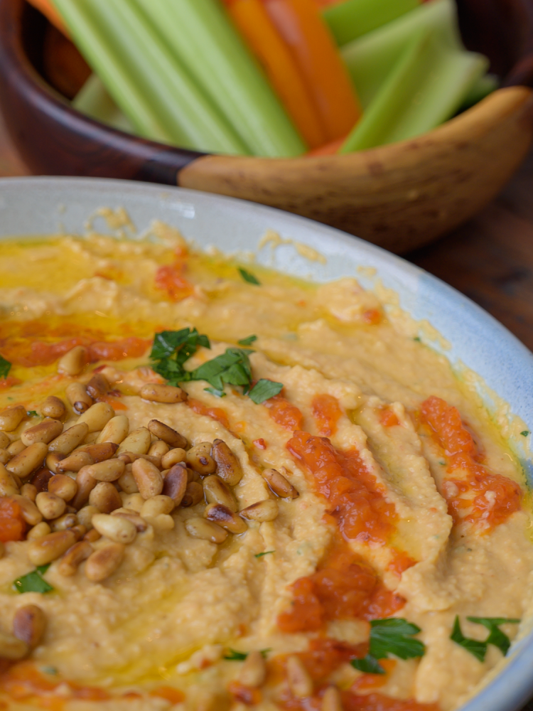 Red Pepper Hummus in a Bowl with Toasted Pine Nuts and Parsley