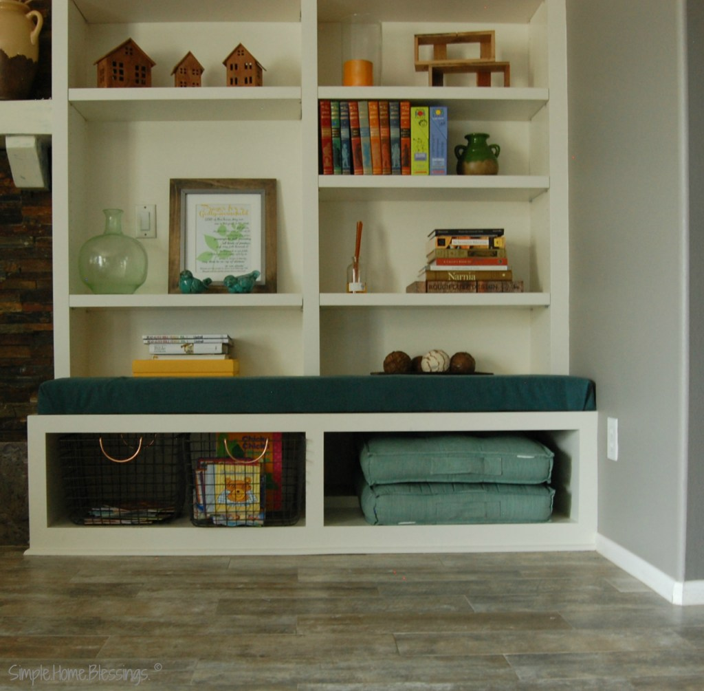 Living Room Organization - adding bins to the bottom shelf to store books and create a reading space