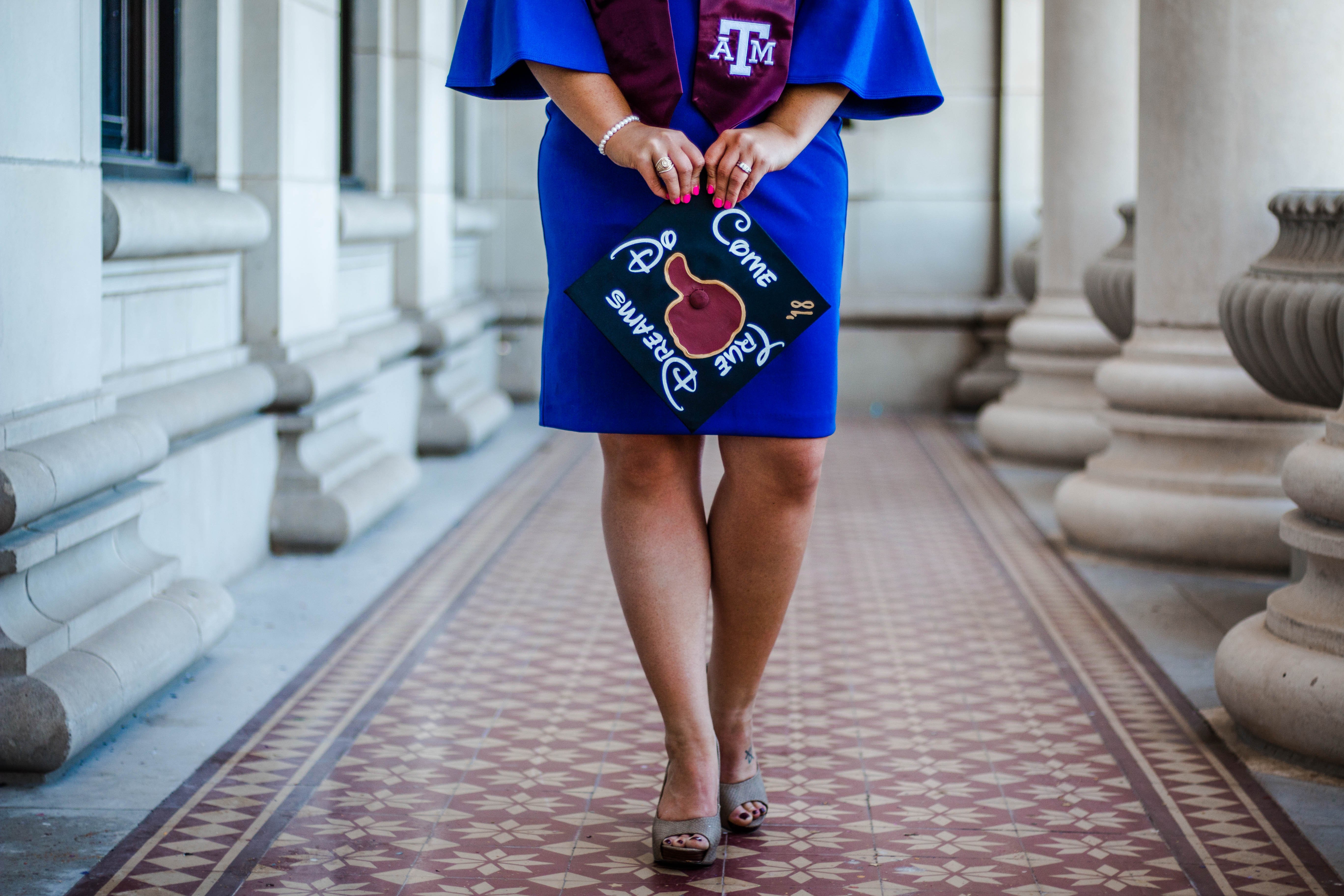 "Graduate holding her cap that reads, ""Dreams do come true""."