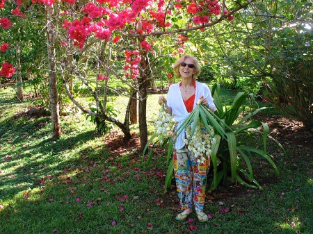 Photograph of Cynthia Adler, wearing some crazy multi-colored pants, and standing under gorgeous red blooms, holding some Flor de Itabo.