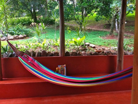 Photograph of a multi-colored hammock hung over the back porch. Parts of the back yard can be seen.