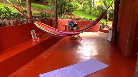 Photograph of the back porch. A yoga mat is on the floor in the foreground, a hammock in the middle distance, and a man reads in a rocking chair in the far corner.