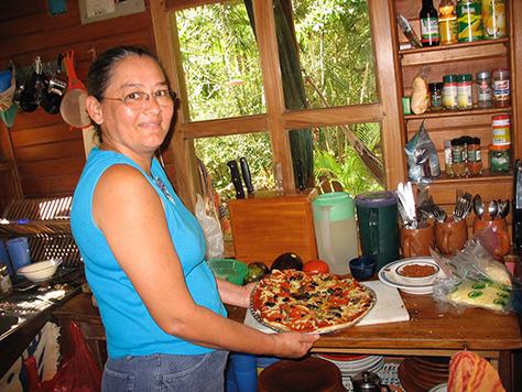 Betty Mora in the kitchen at Refugio de Los Angeles presenting a homemade pizza